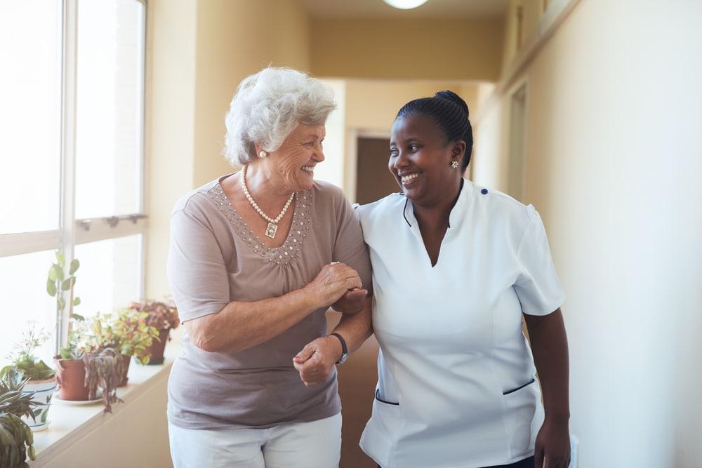 a caregiver walking/helping a senior at a senior living facility