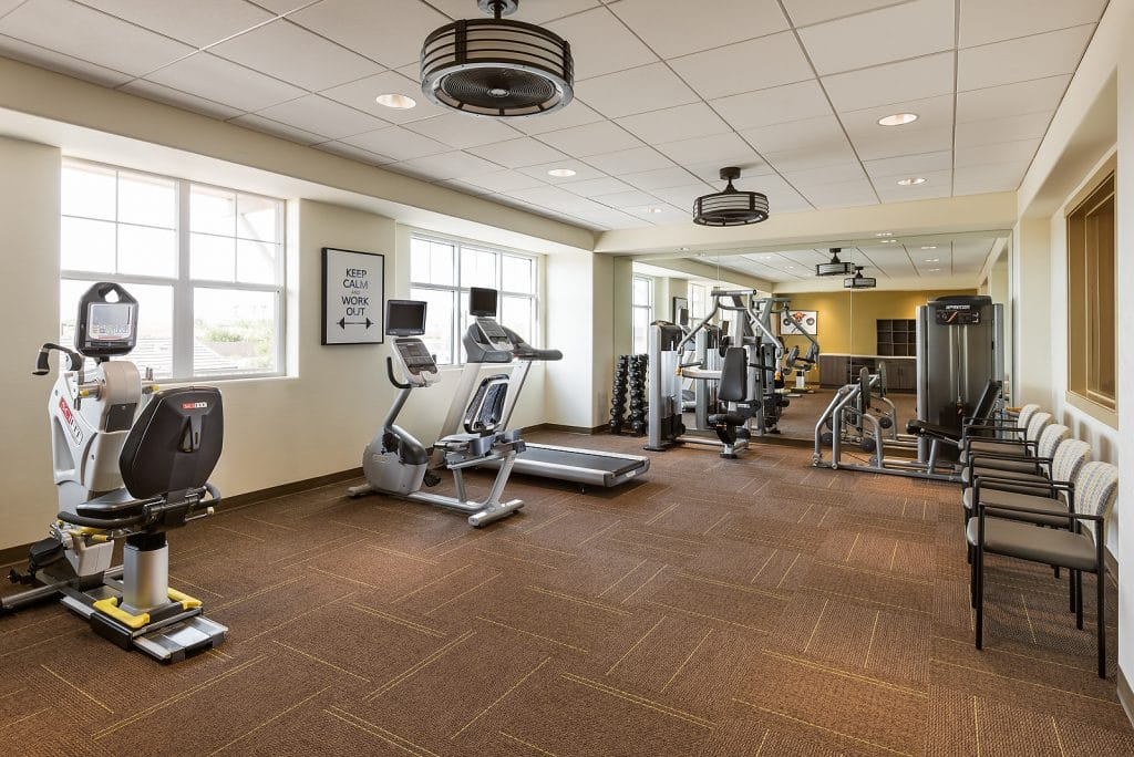 A gym in a senior home with cardio and weight exercise machines