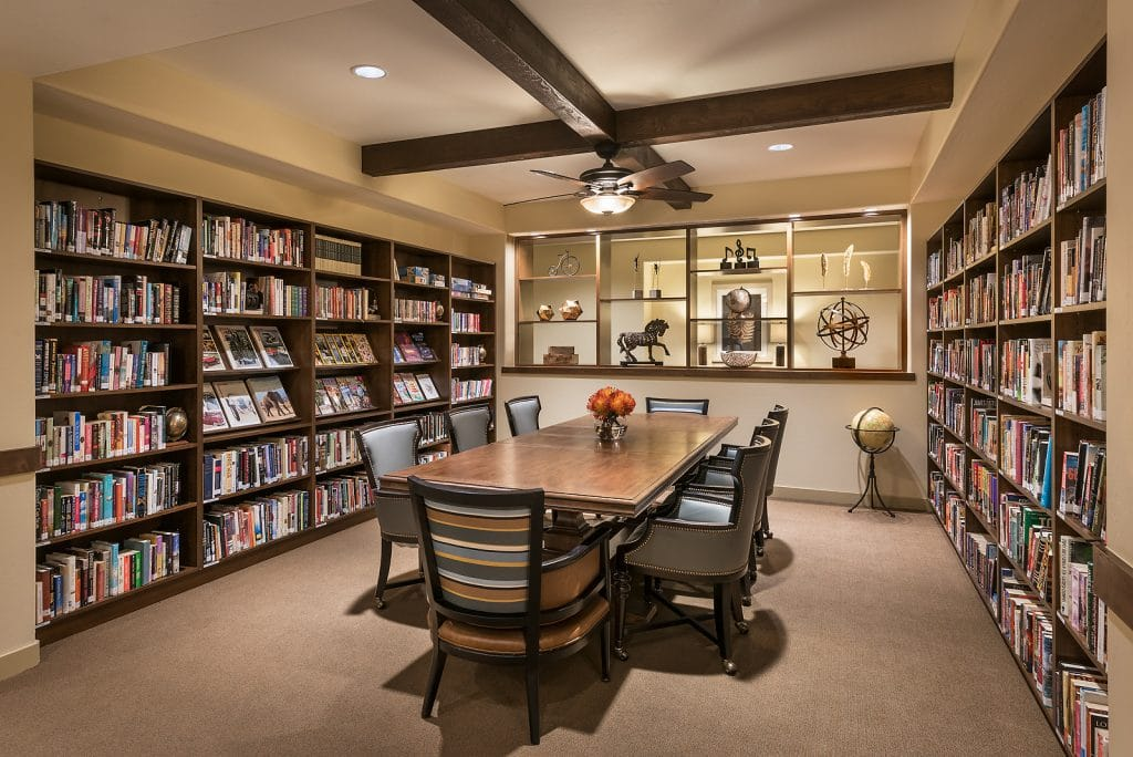 A library room with books, tables, chairs, and decorations for interior design