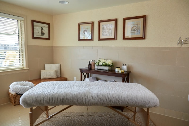 Spa and massage room with soothing interior decor colors, fabrics and artwork