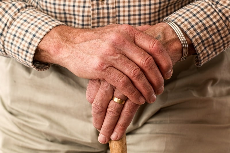 hands of an older man with a walking stick