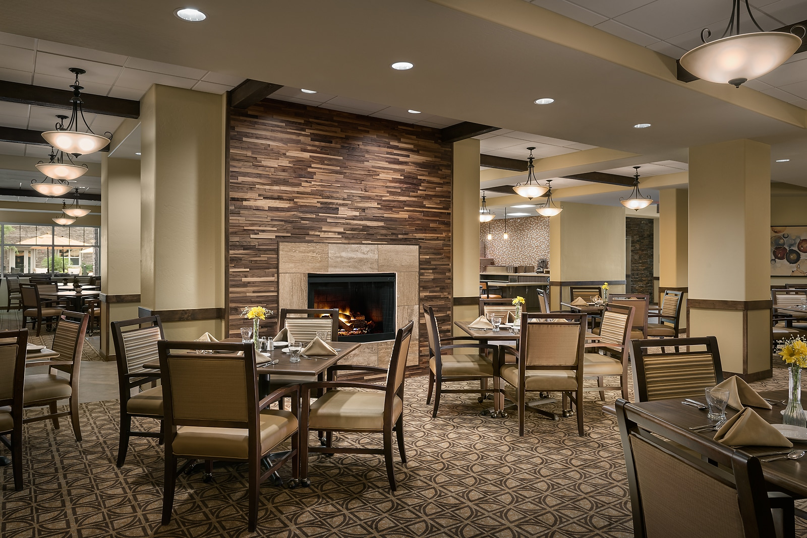 A fireplace and dining tables in the dining room of a senior living facility