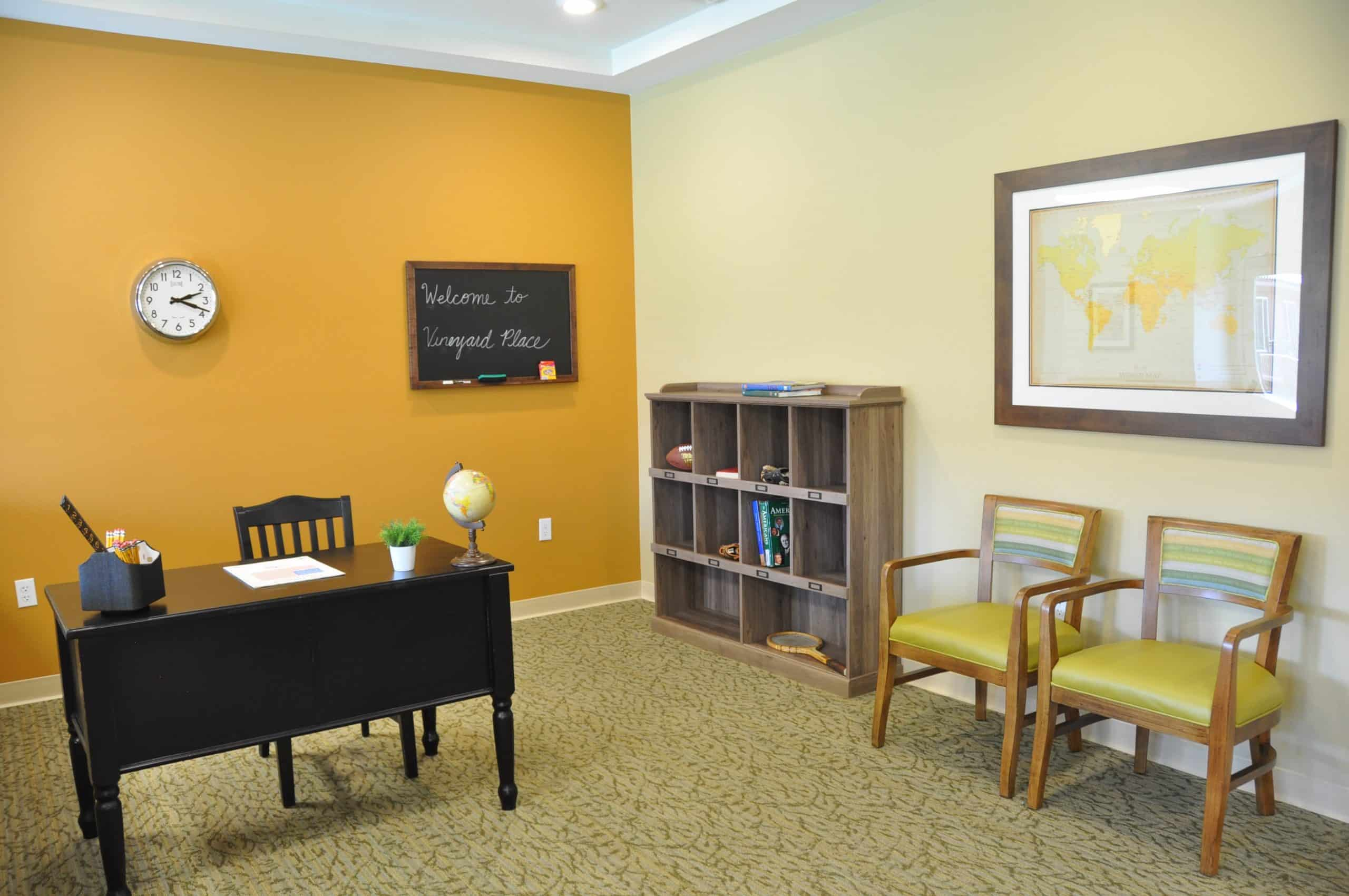 a teacher's desk and bookcase as an example of a life skills station at a memory care community