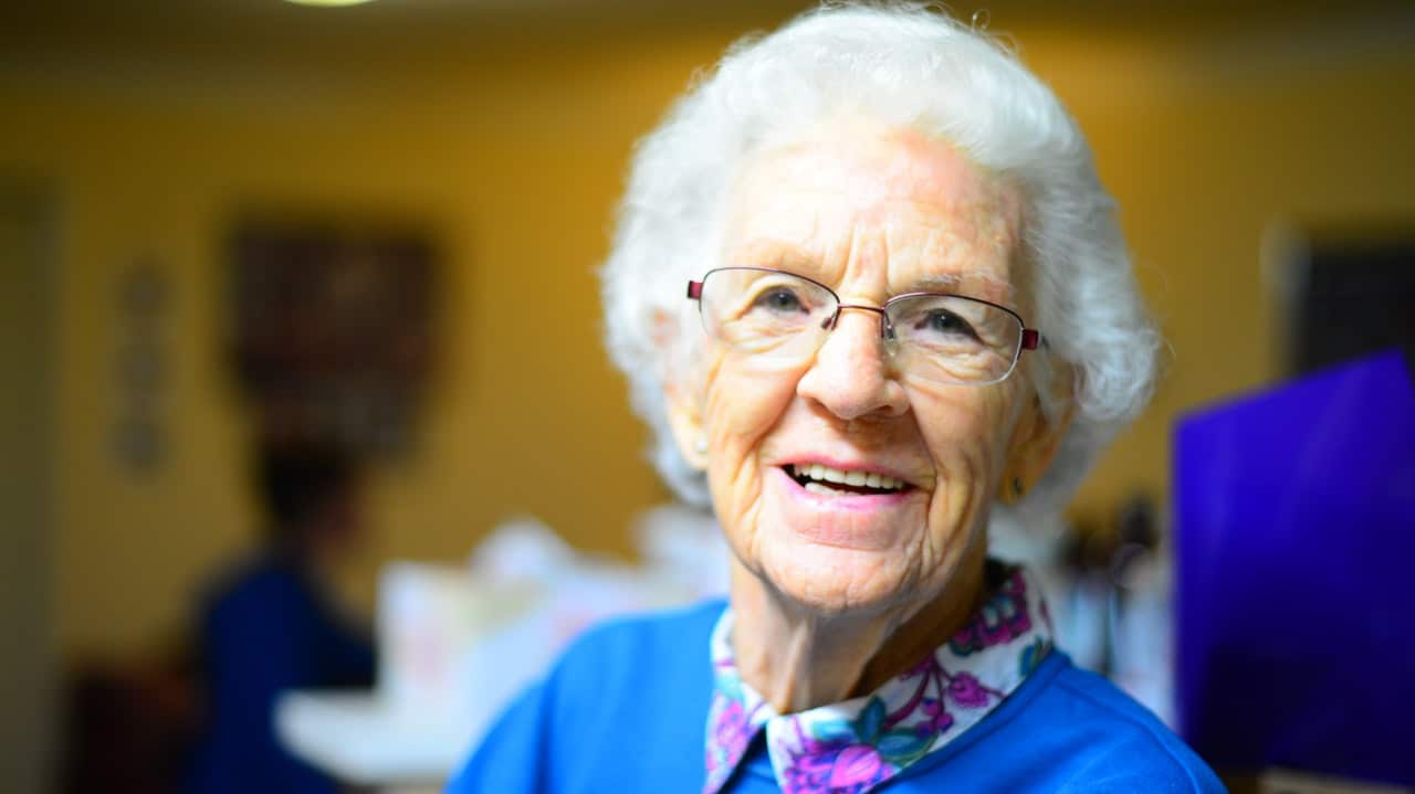 smiling elderly female at senior living designed community